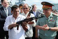 Philippine President Rodrigo Duterte (l) holds a AK-47 assault rifle as Russian Minister of Defence Sergei Shoigu looks
