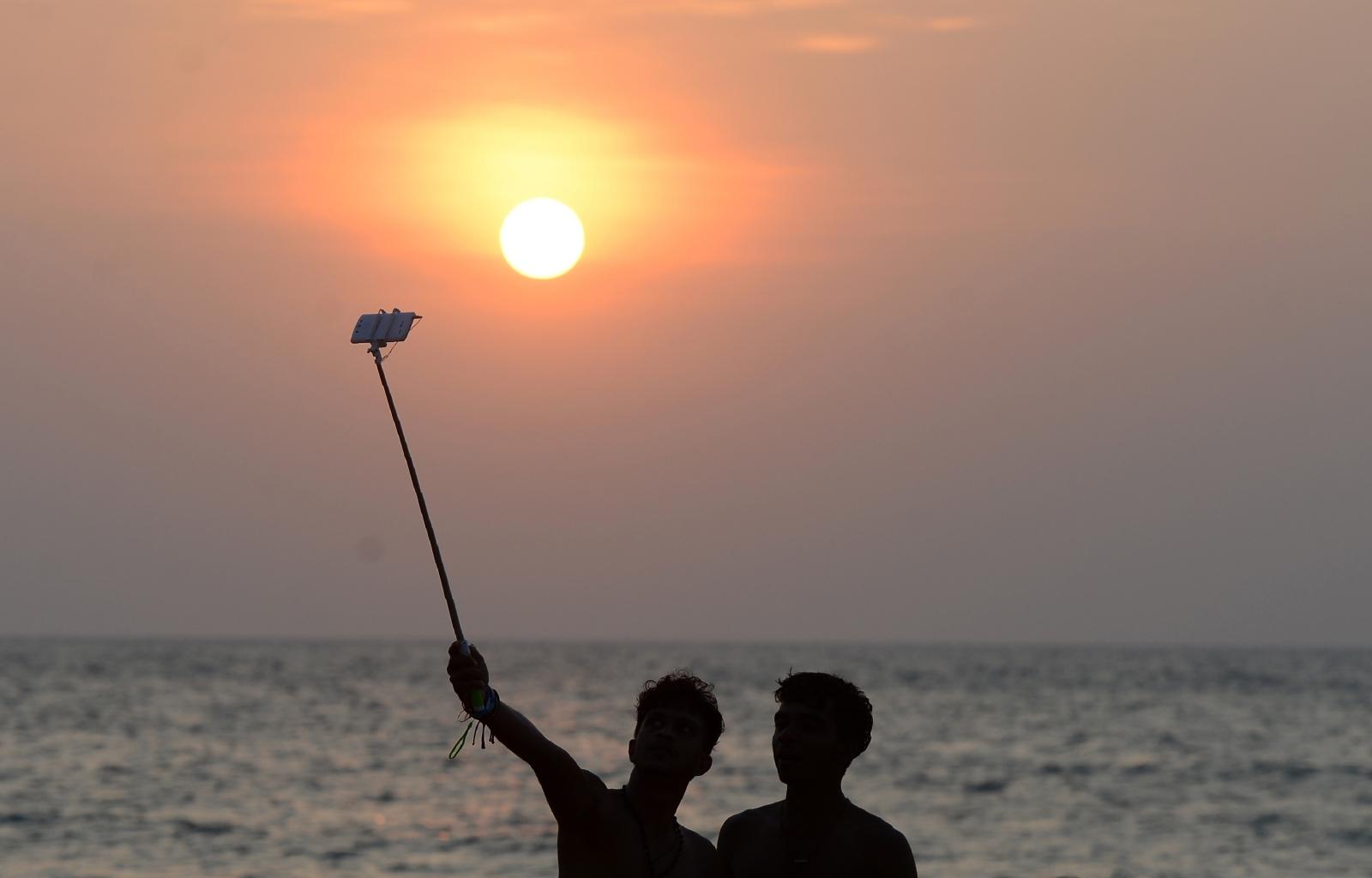 Men take a selfie by the beach
