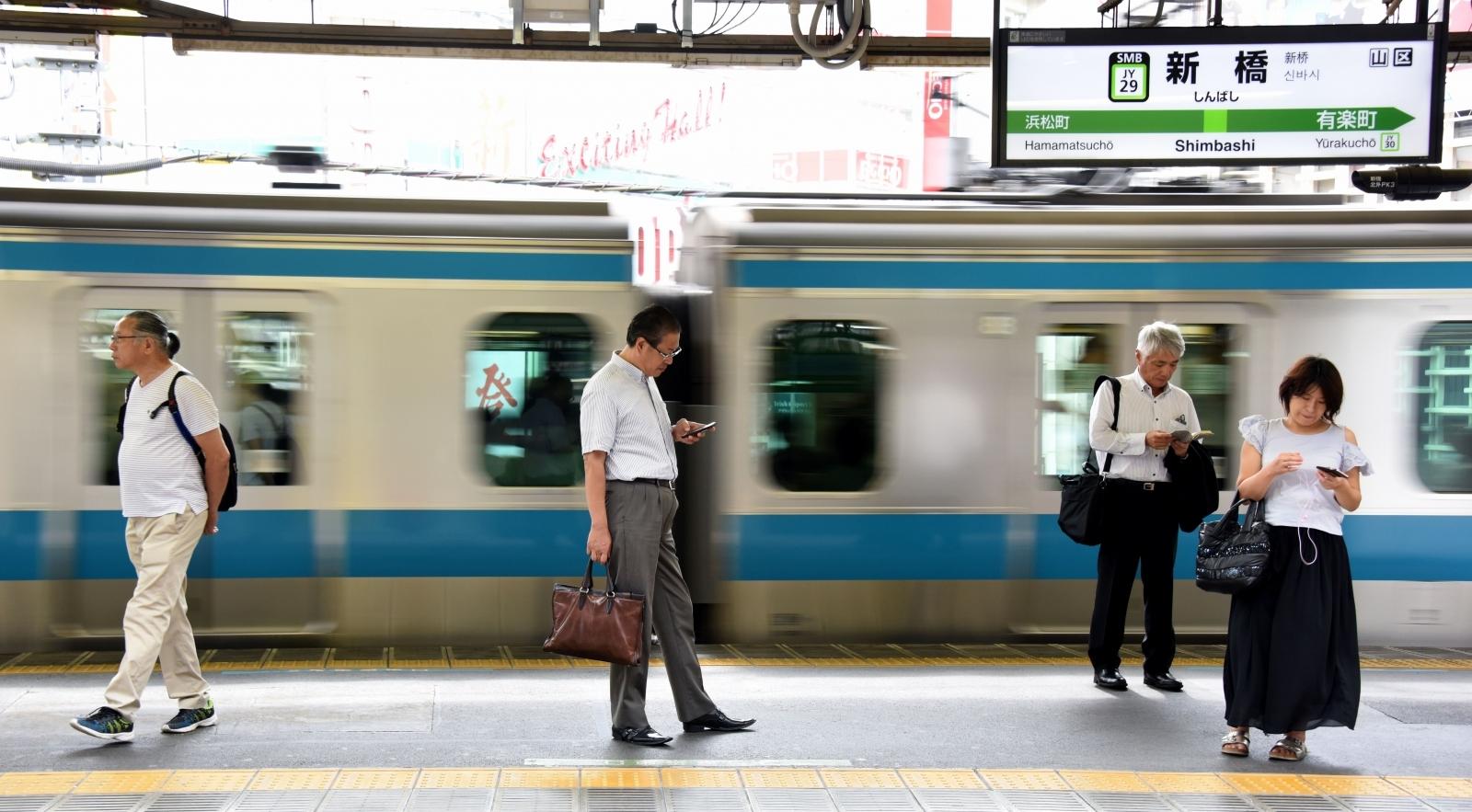 People using smartphones on Japanese train platform