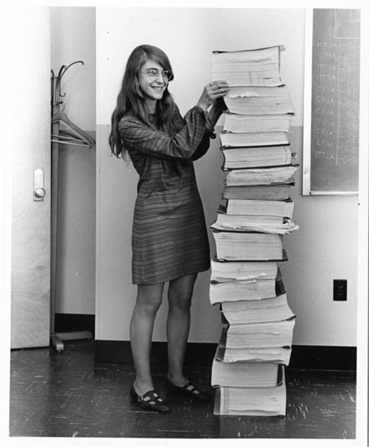 Margaret Hamilton stands beside source code