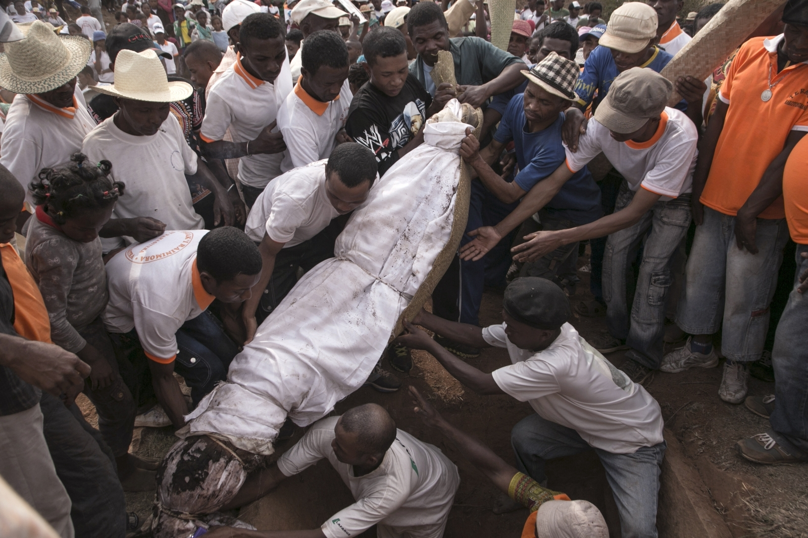 People carry a body wrapped in a sheet as they take part in a funerary tradition called the Famadihana in the village of Ambohijafy, a few kilometres from Antananarivo, on September 23, 2017.