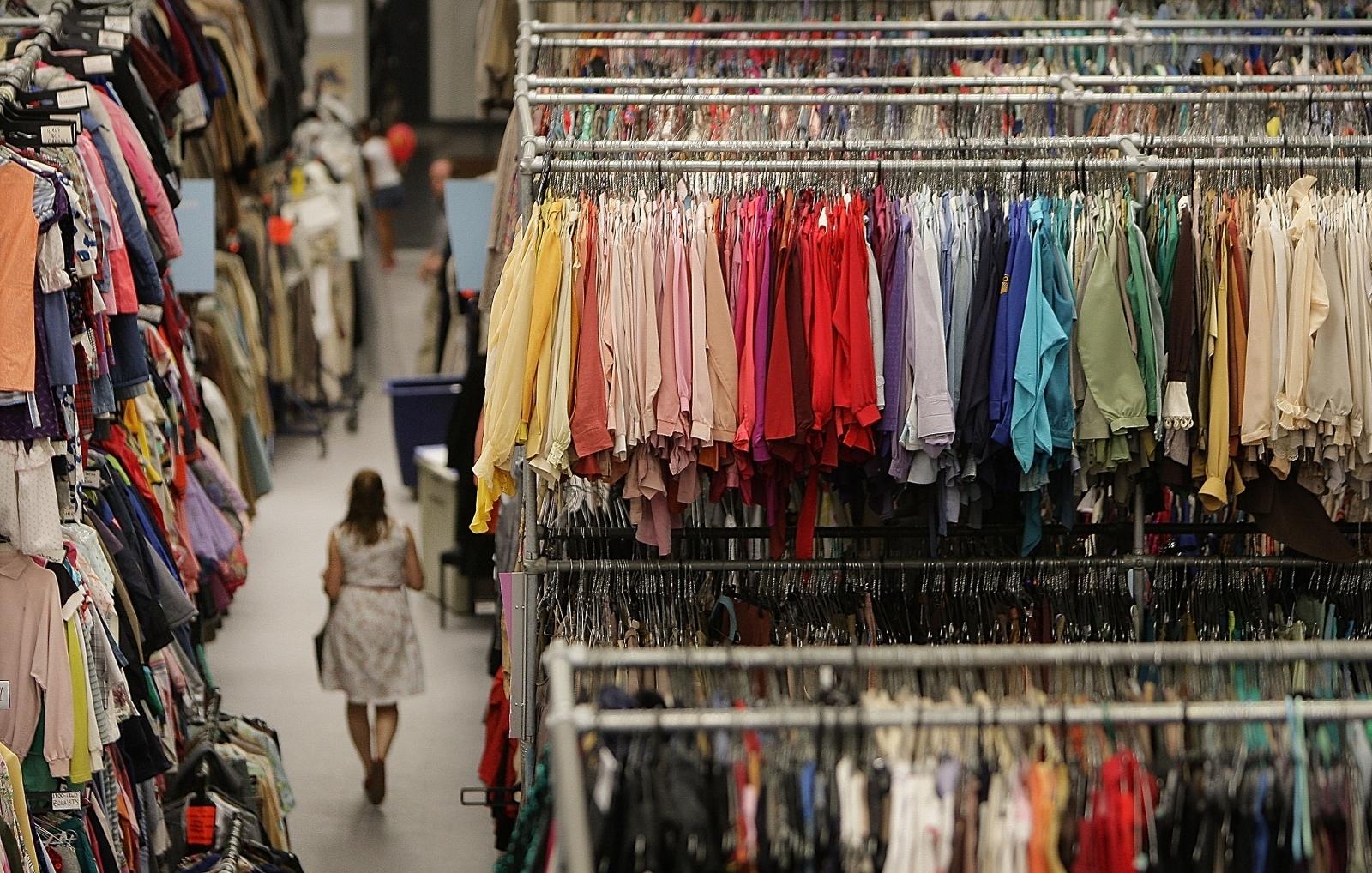 A woman walks between racks of clothes