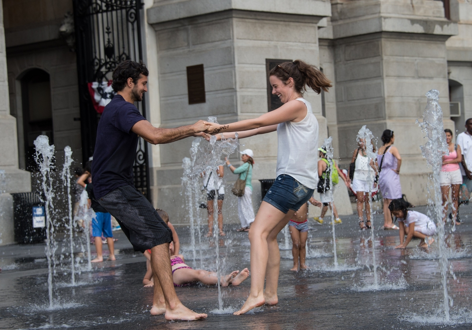 A couple plays in a fountain in front of City Hall in Philadelphia, but dating relationships across the US have become more complicated based on views around US President Donald Trump