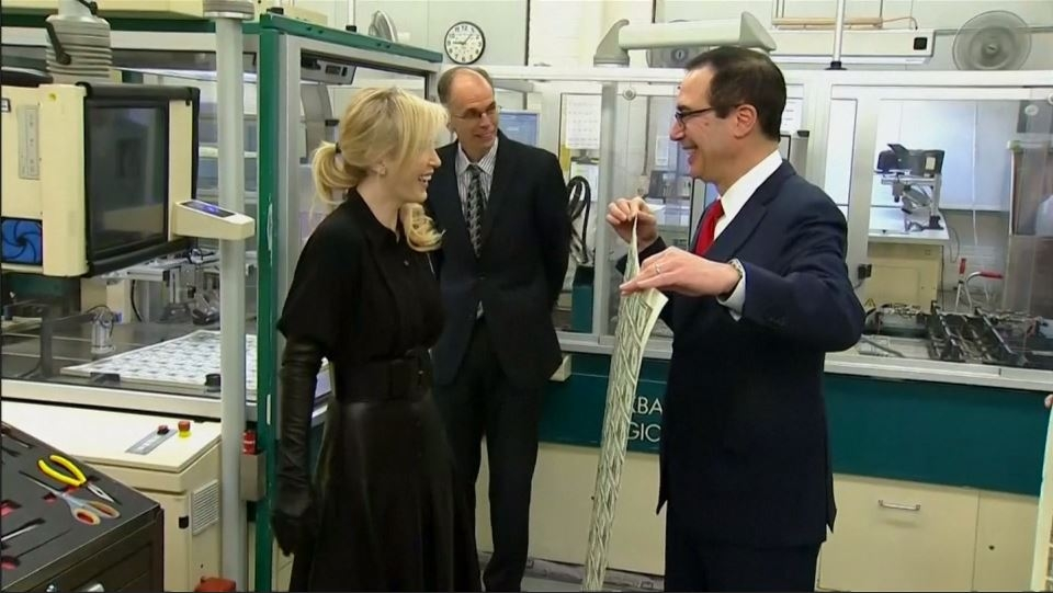 US Treasury Secretary Steve Mnuchin and wife Louise Linton pose for photos with dollar bills
