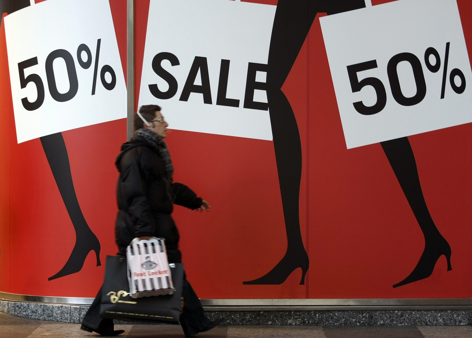 Man walks past sale shopping signs
