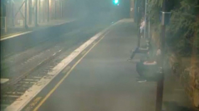 Dramatic footage shows woman pulled away from oncoming train with seconds to spare