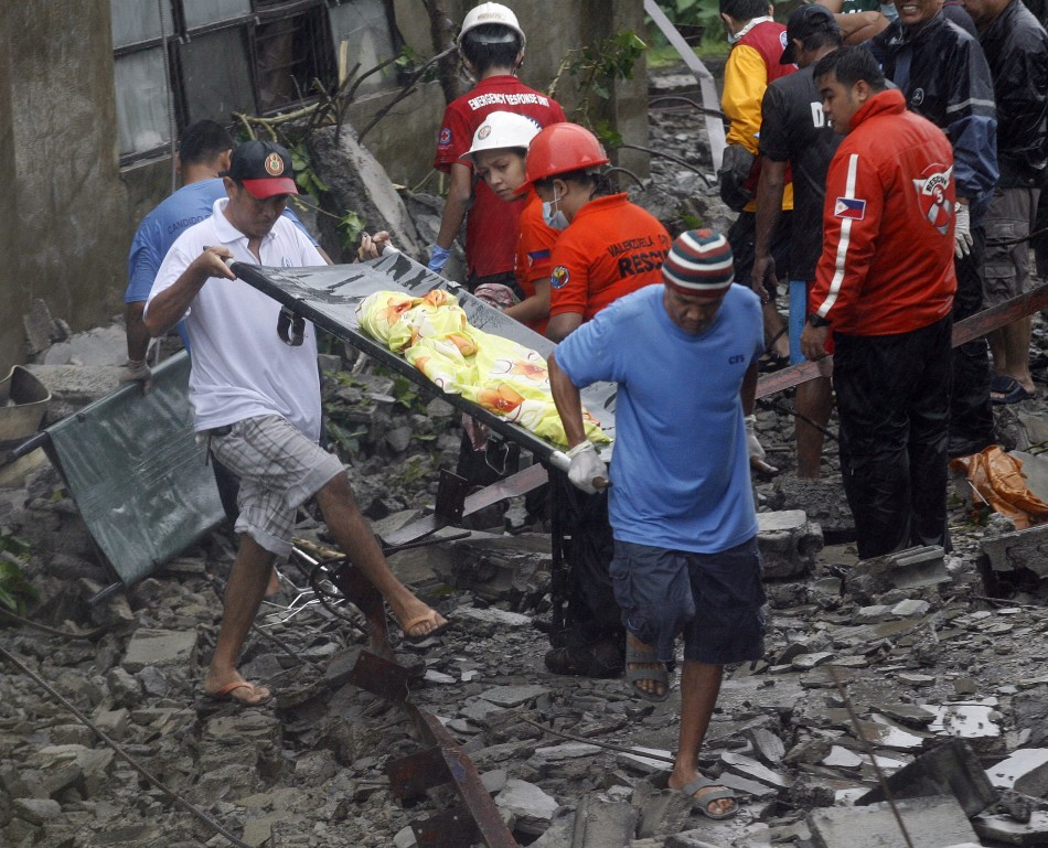 Rescuers recover a body from the rubble after strong winds brought by Typhoon Nesat, locally known as Pedring, knocked down a wall killing four residents in Valenzuela City Metro Manila 27/09/2011