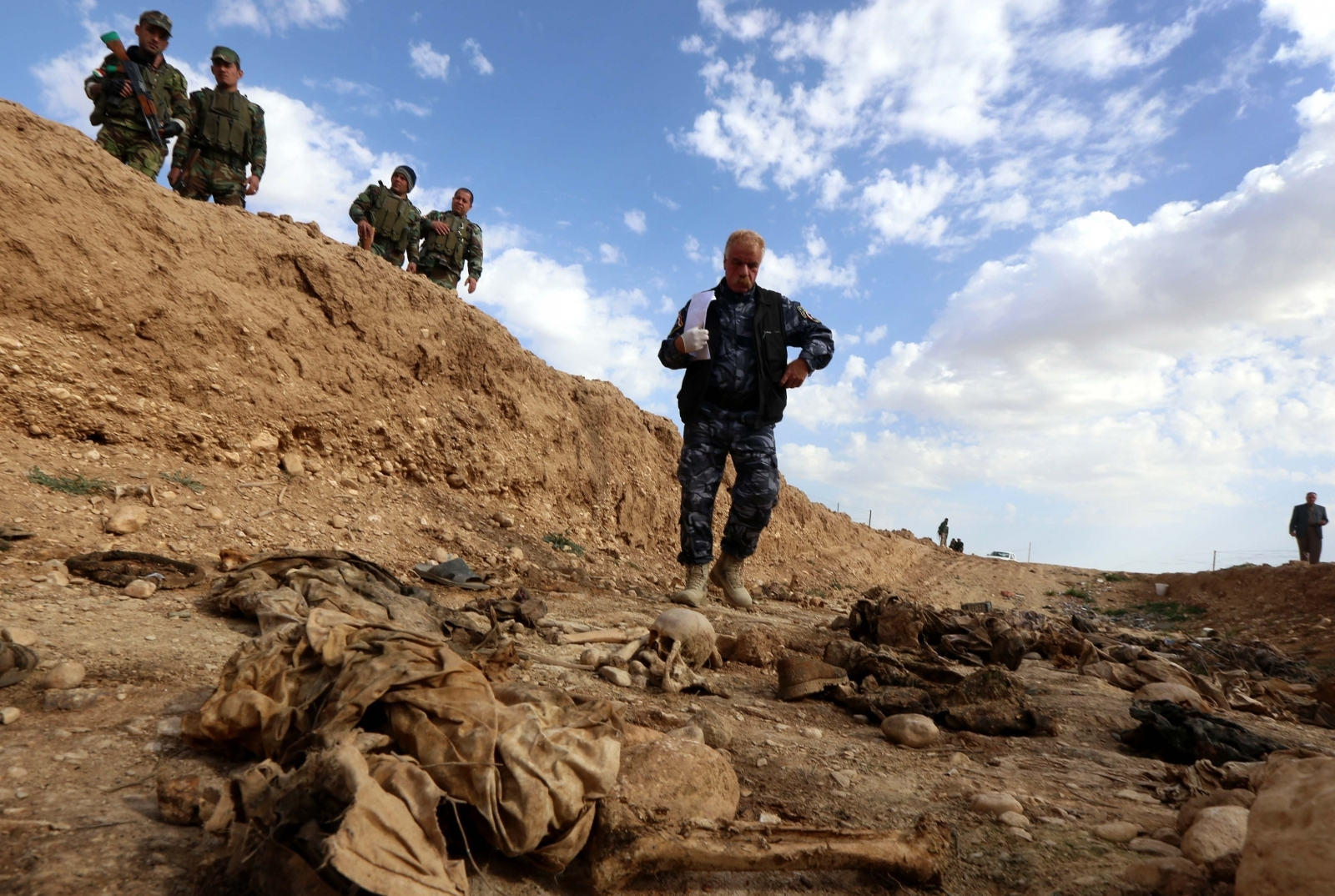 Kurdish forces look at the remains of Yazidis killed by the Isis jihadist group