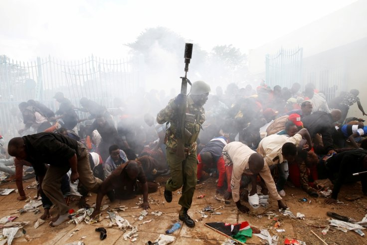 A crowd scatters as police fire tear gas to try control a crowd trying to force their way into the inauguration of President Uhuru Kenyatta at Kasarani Stadium in Nairobi, Kenya