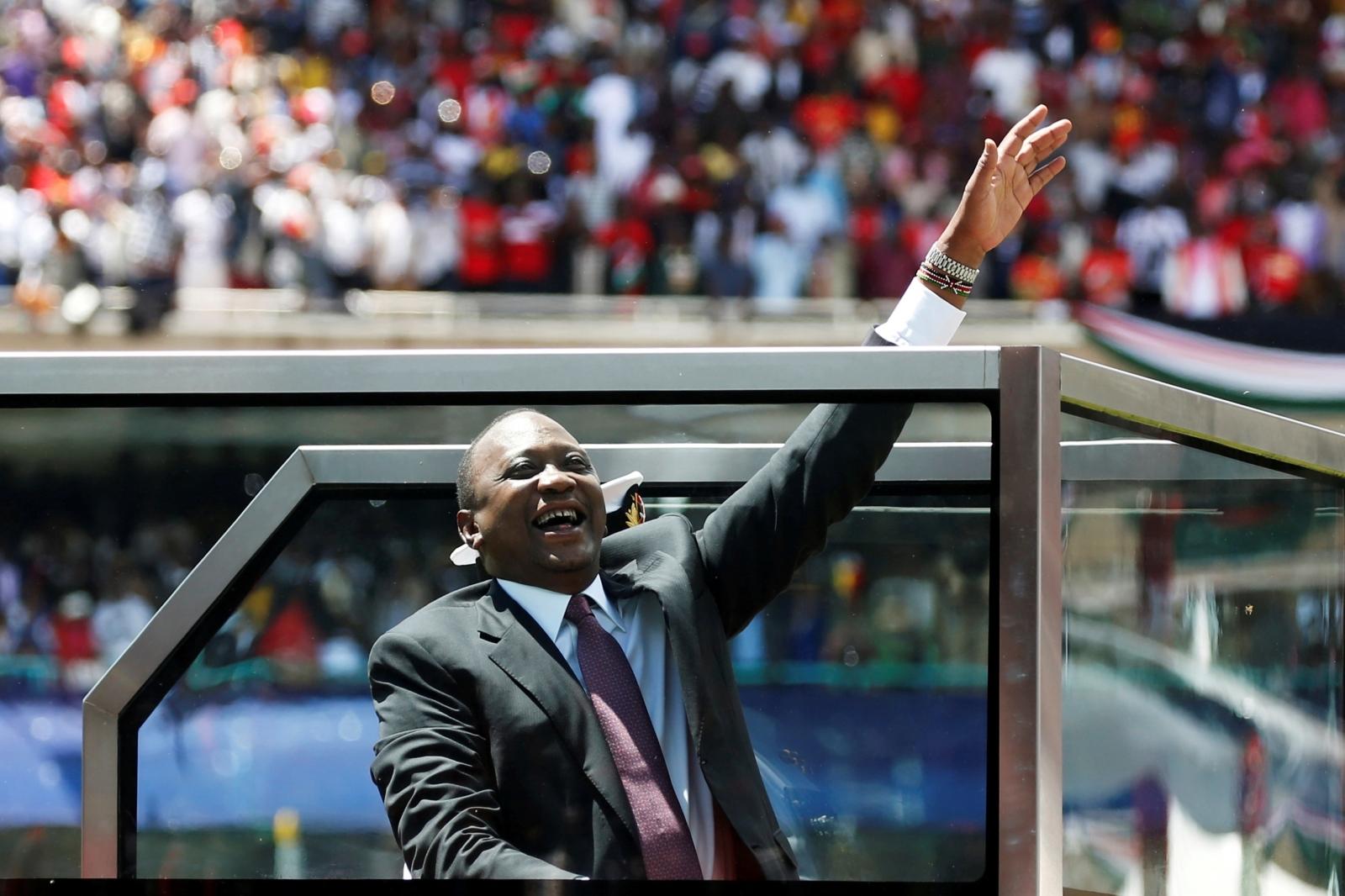 Kenya's President Uhuru Kenyatta waves upon his arrival to his inauguration ceremony where he will be sworn in as president at Kasarani Stadium in Nairobi, Kenya