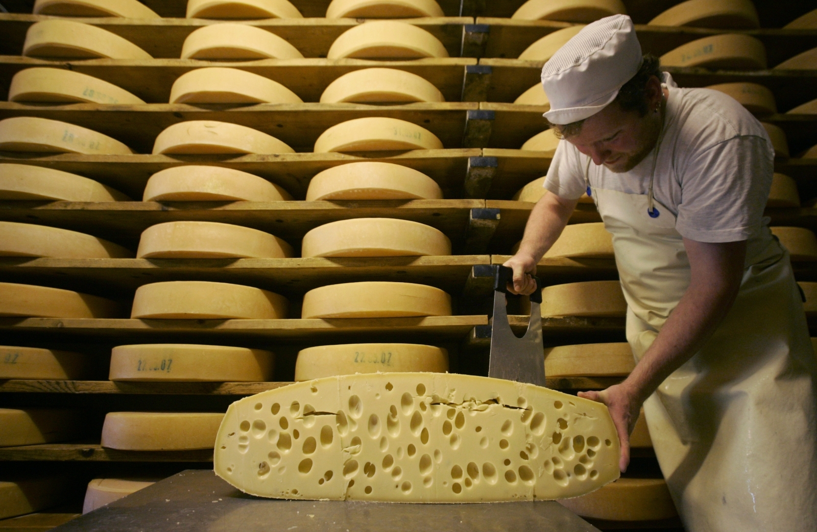A cheese maker carves cheese