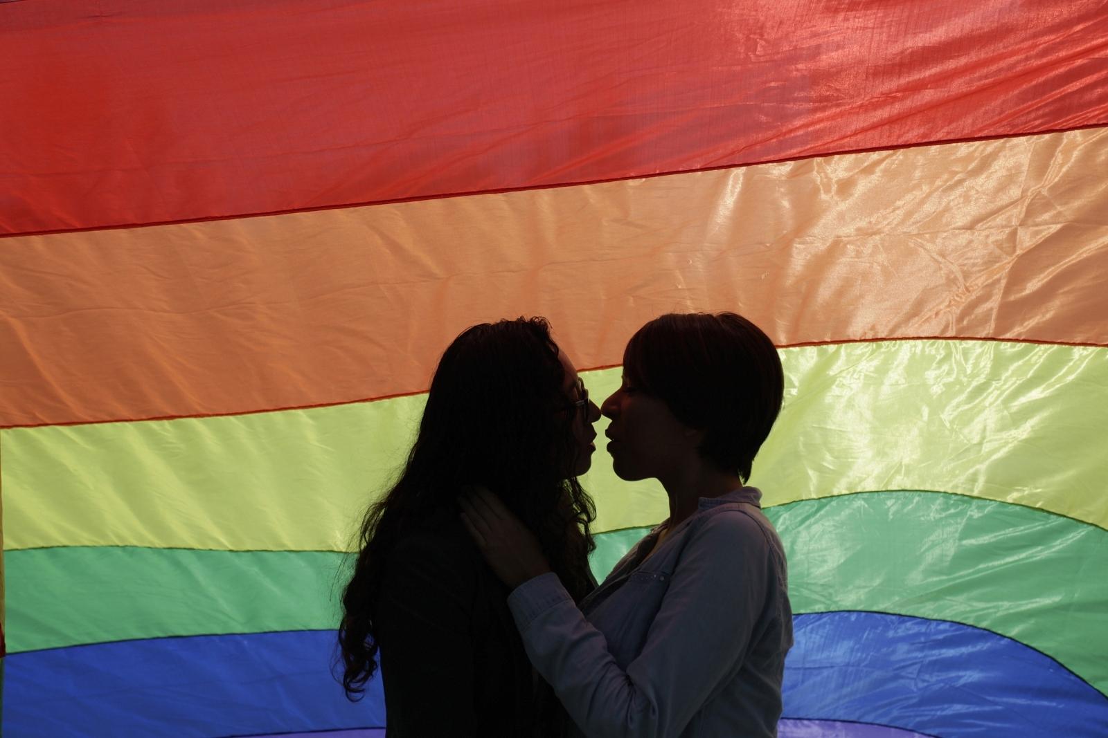 Gay couple kisses by rainbow flag