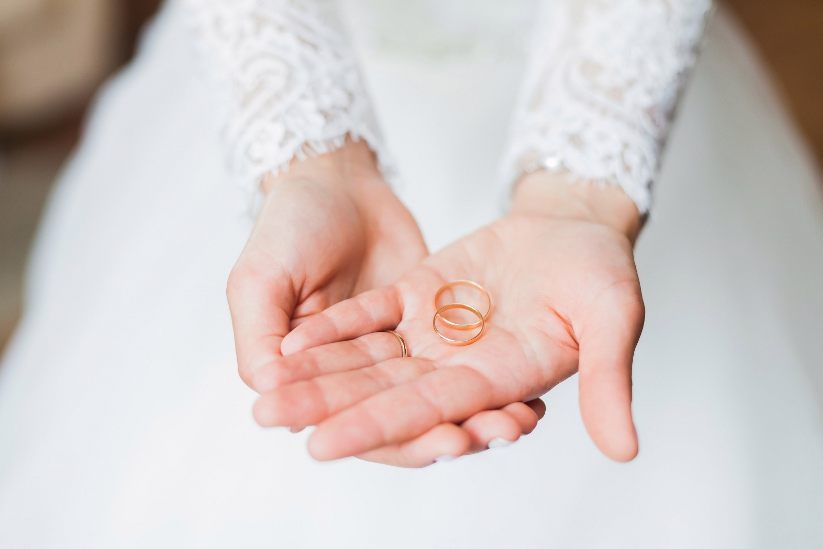 A bride holds wedding rings