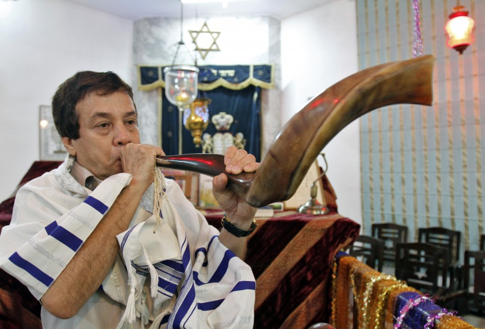 Ezekiel Isaac Malekar, honorary secretary of the Judah Hyam Synagogue synagogue, poses with a shofar horn inside the synagogue in New Delhi