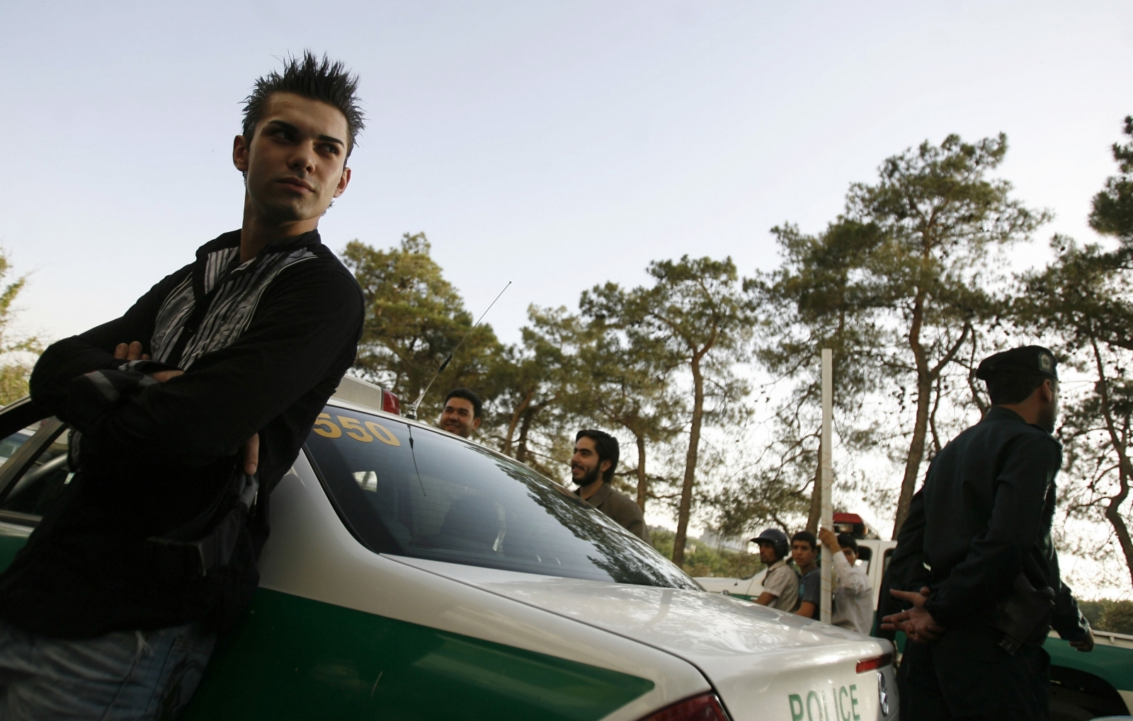 A youth leans against a police car after being detained for a Western-style haircut in Tehran
