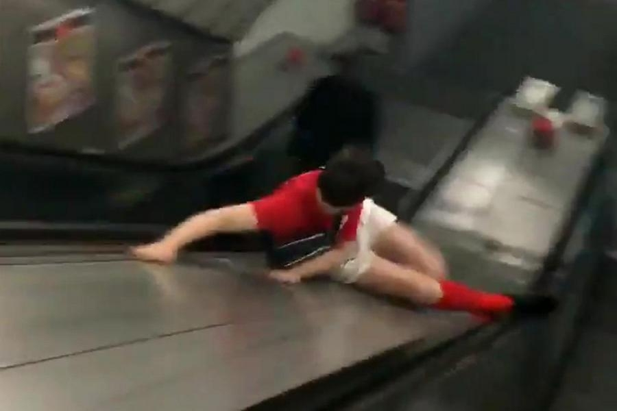 Darts fan Freddie Andrews takes the quick route down a London Underground escalator at London Bridge station