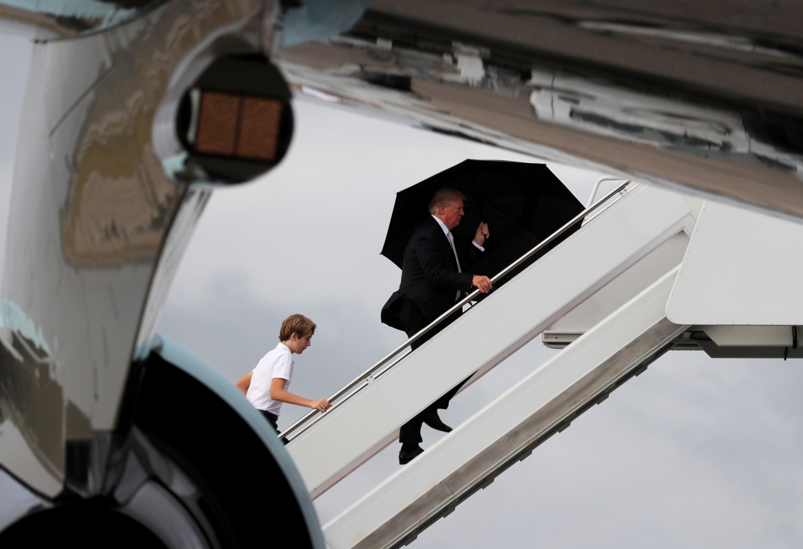 US President Donald Trump and his son Barron with his wife Melania behind (out of shot) board Air Force One as he departs West Palm Beach, Florida