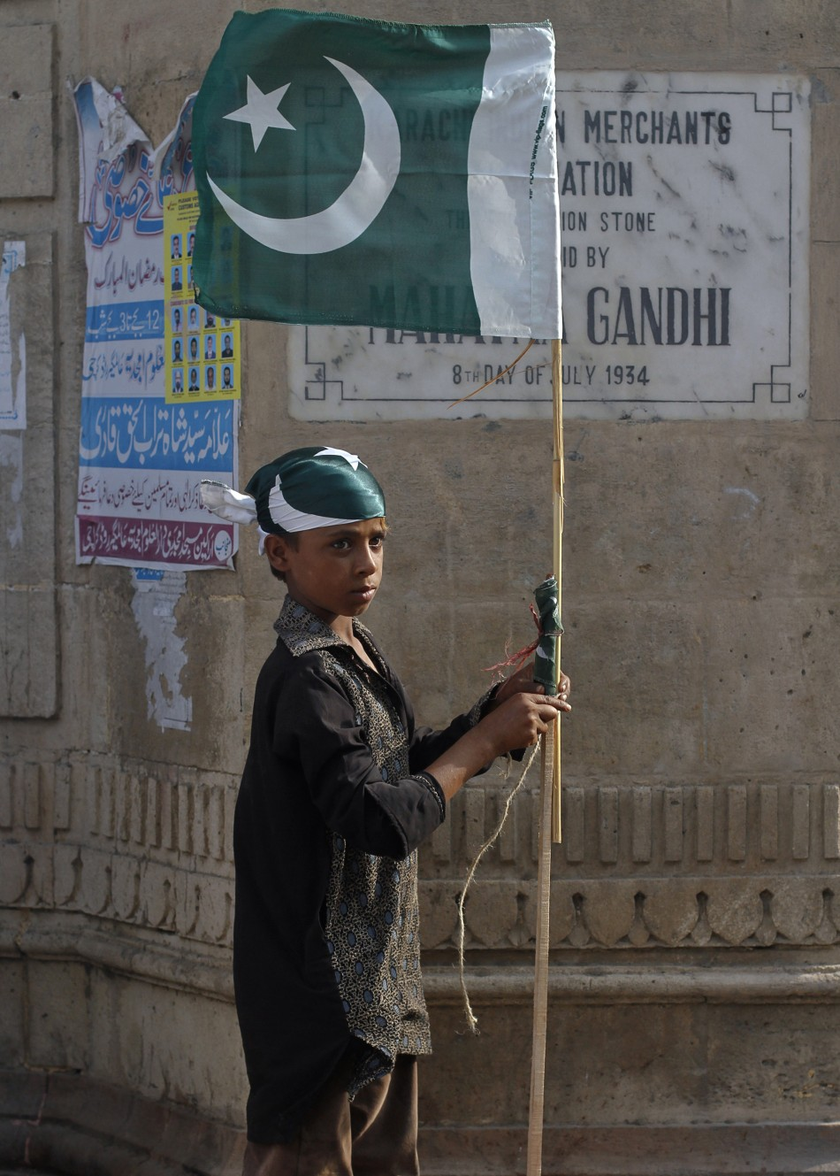 A boy ties up a Pakistan national flag to a bamboo stick as some of nearly a dozen traders near by taking part in an anti-American demonstration in Karachi