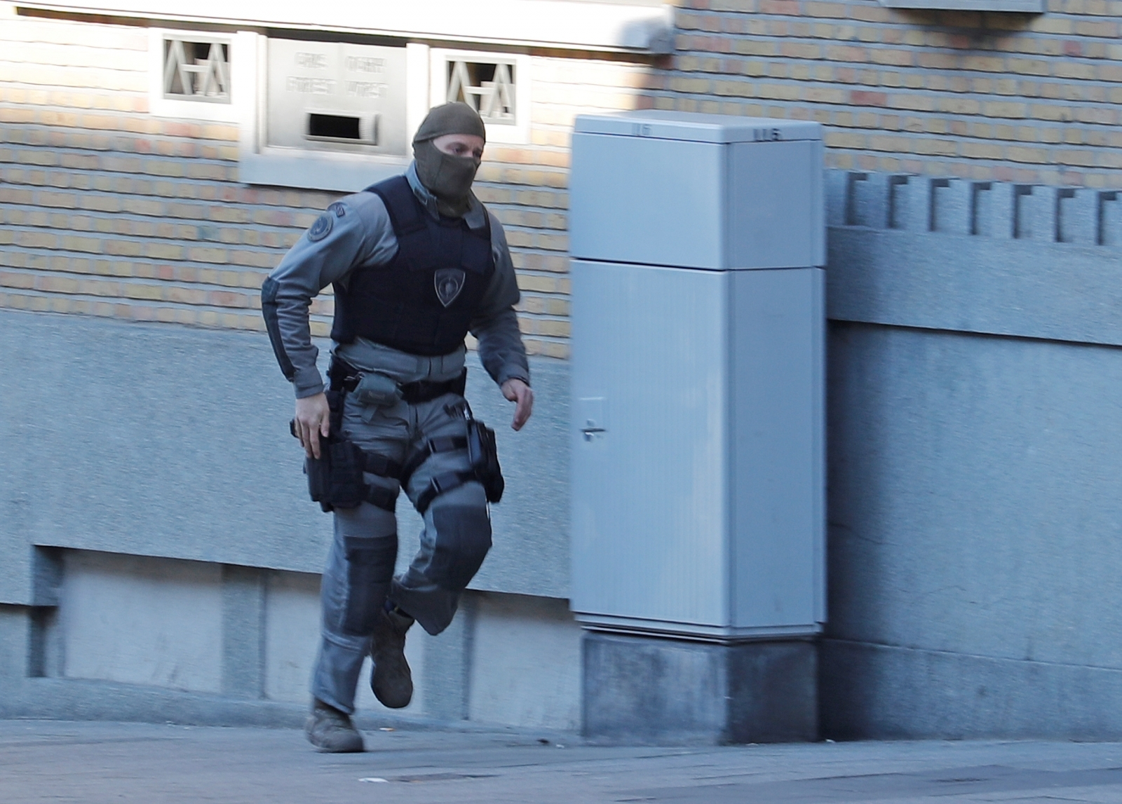 A Belgian police special forces officer runs in the Forest district after it was closed by Belgian police hunting a gunman