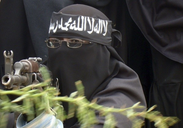 A woman Al Shabaab fighter points a gun during a demonstration, against the African Union Mission in Somalia.