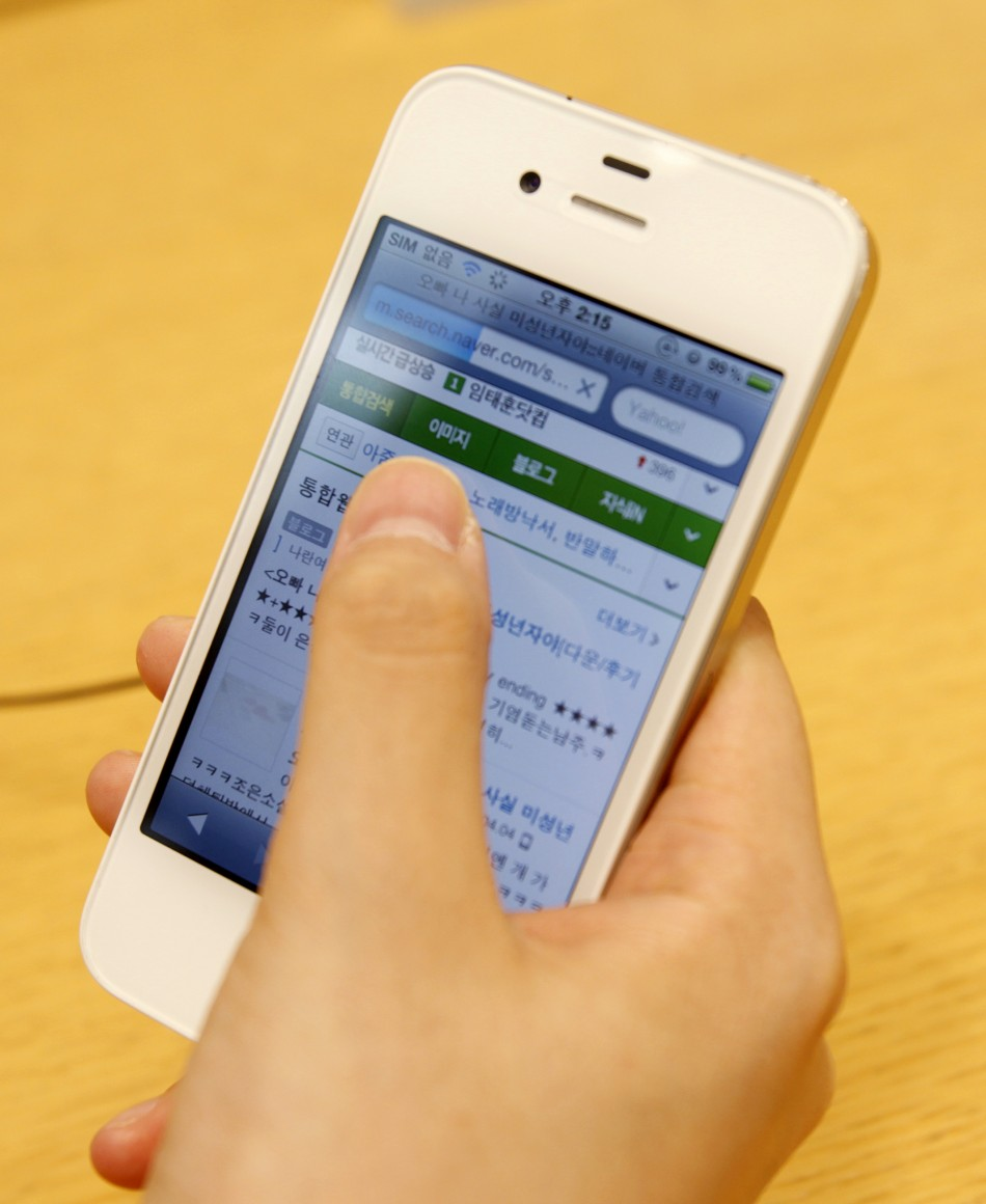 A woman uses an Apple iPhone 4 smartphone for Web surfing