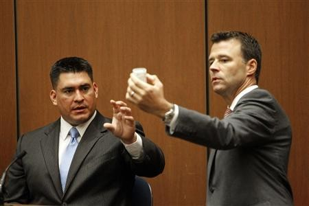 Deputy District Attorney David Walgren (R) holds a bottle of propofol introduced as evidence as he questions Alberto Alvarez (L), one of Michael Jackson's security guards, during Dr. Conrad Murray's trial in the death of pop star Michael Jackson