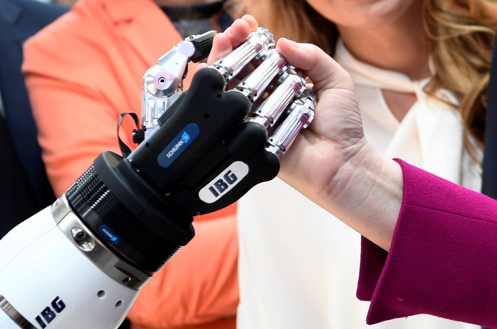 German Chancellor Angela Merkel shakes hands with a humanoid robot