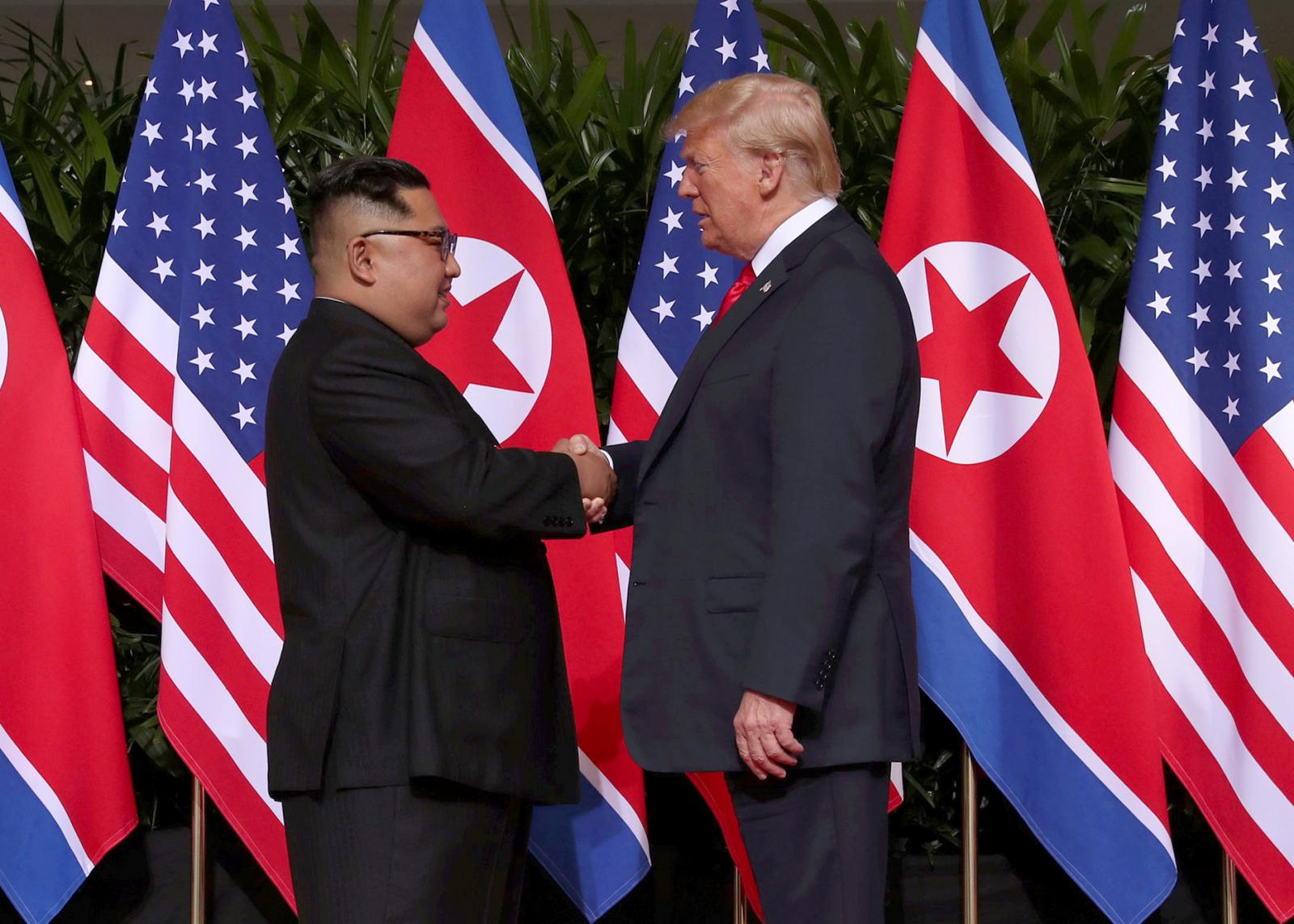 Donald Trump shakes hands with Kim Jong Un