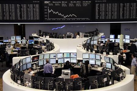 Traders work at their desks in front of the DAX board at the Frankfurt stock exchange