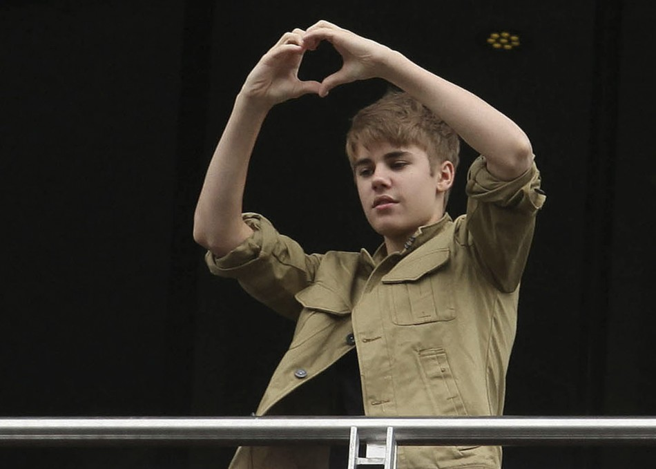 Justin Bieber greets fans from balcony of his hotel before leaving for his first My World Tour concert at Foro Sol in Mexico City