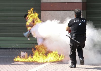 A policeman tries to extinguish a fire on a man after set himself ablaze outside a bank branch in Thessaloniki in northern Greece