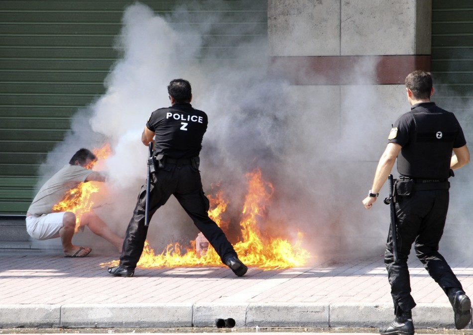 A policeman tries to extinguish a fire on a man after he set himself ablaze outside a bank branch in Thessaloniki in northern Greece