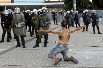 A protester confronts riot police guarding the entrance to Thessalonikis International Trade Fair during a protest against austerity