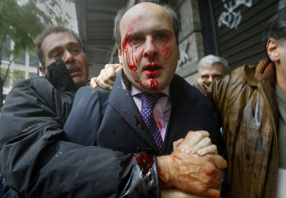 Former conservative minister Kostis Hatzidakis is covered with blood in central Athens