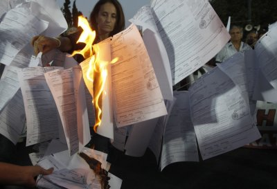 Protesters from Greek Communist-affiliated trade union PAME burn bills for new one-off income tax during rally against governments new austerity measures in Athens