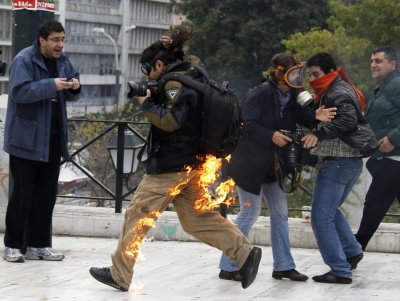 A photographer is seen in flames as he tries to escape after he caught fire from a petrol bomb during riots in front of the parliament in Athens