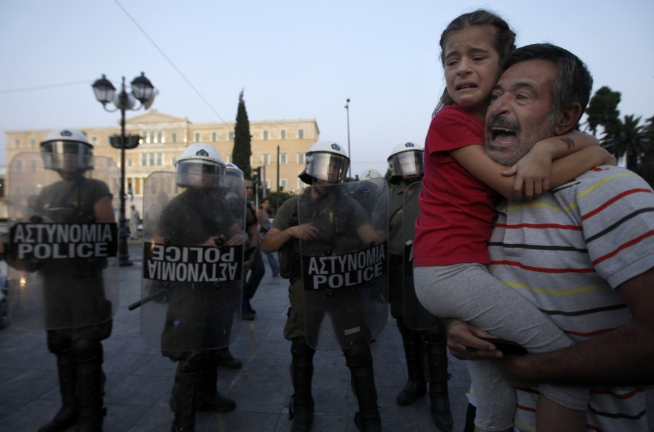 A protester, with a crying girl in his arms, shouts at riot police during a rally in Athens