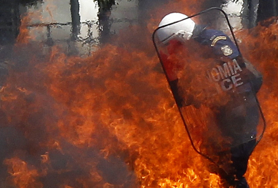 Policemen try to escape a fire from a petrol bomb during riots at May Day rally in Athens