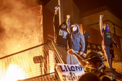 Protesters hold up their fists as flames rise behind them