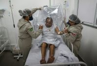Health workers  assist a COVID-19 patient