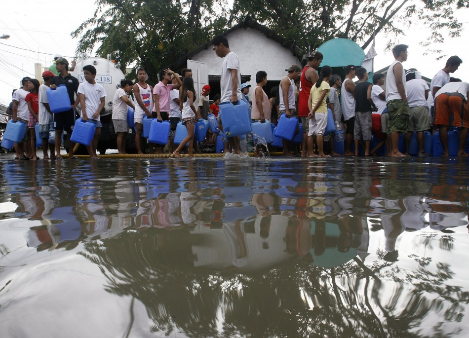 Villagers queue for drinking water at a partially flooded street in Hagonoy, Bulacan province
