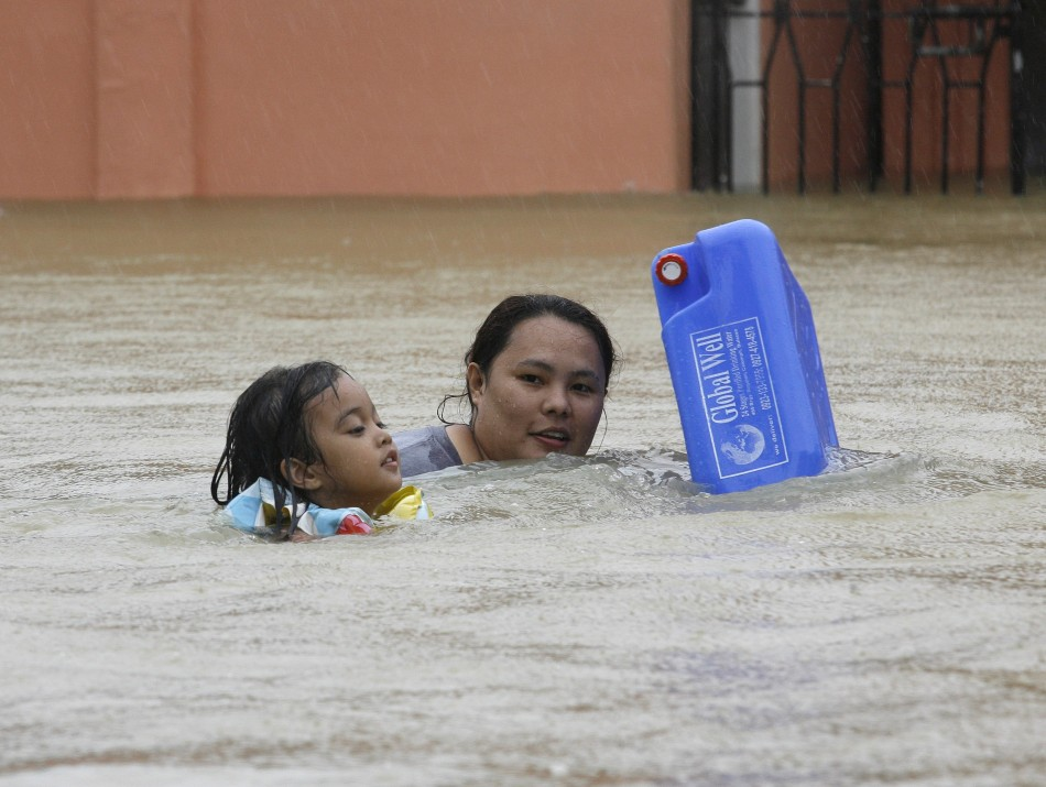 A mother And Child Wade Through Floodwater To Get Drinking Water
