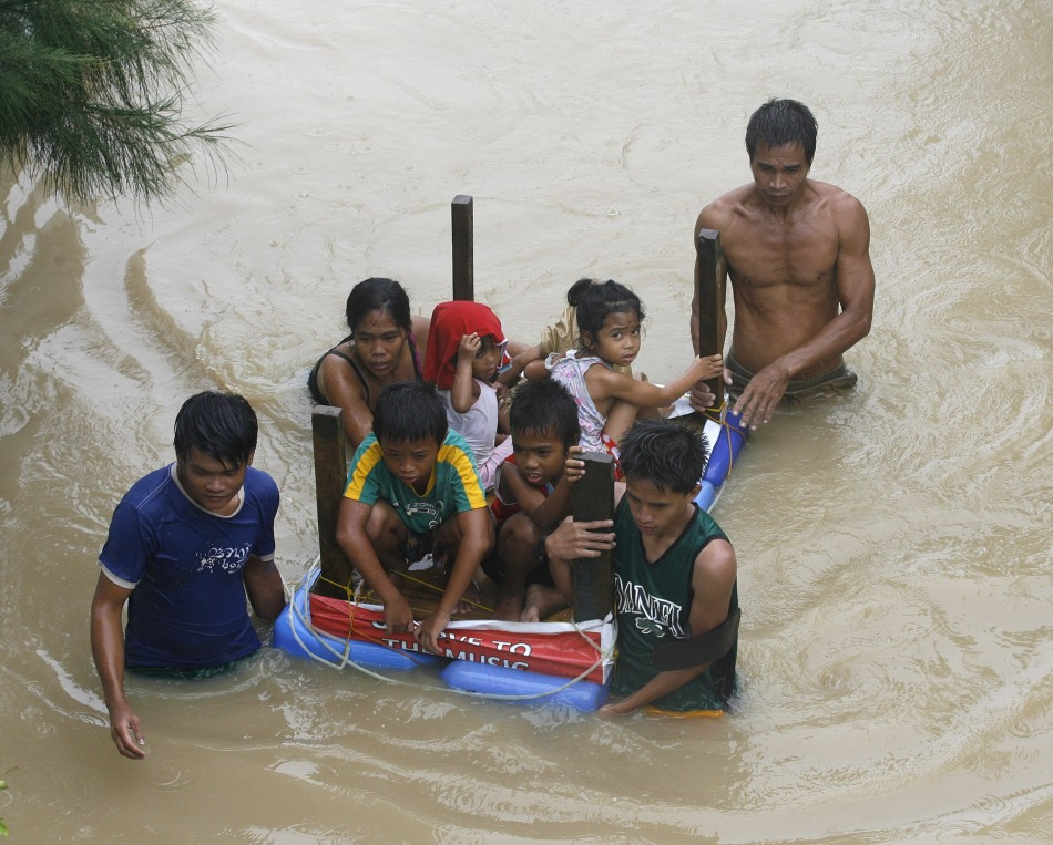 Typhoon Nalgae Hits Philippines - 04 Oct 2011: 9 A Family Uses A Table As A Makeshift Raft To Evacuate Their Children