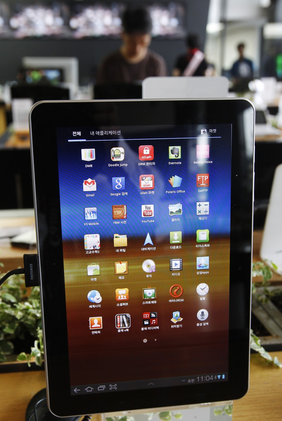A customer looks at smartphones behind a Samsung Electronics' Galaxy Tab 10.1 on display in Seoul