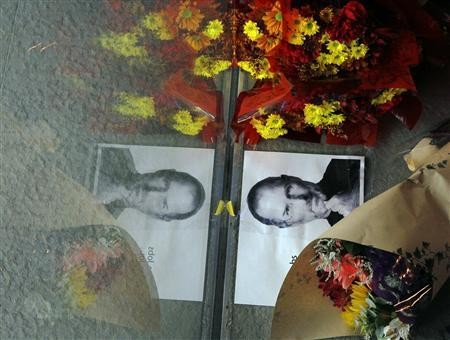 Flowers and a photograph of Steve Jobs are placed against the window outside an Apple store in Boston, Massachusetts