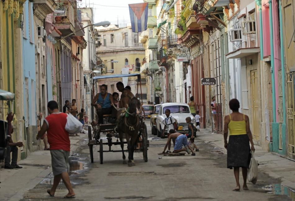People walk as children play on a street in Havana, Cuba
