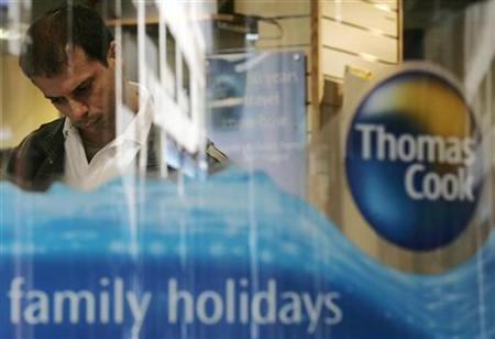 A man looks at a travel brochure of travel company Thomas Cook in London