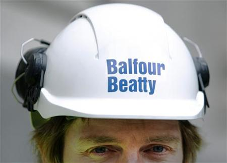 A Balfour Beatty worker walks onto a site in London