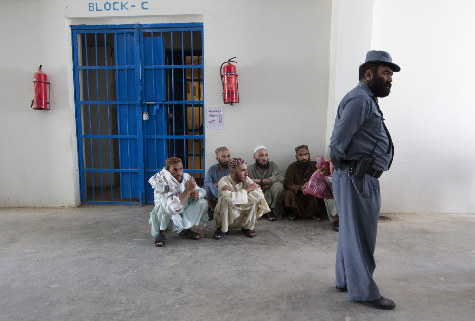An Afghan policeman stands in front of inmates in a prison in the town of Lashkar Gah in Helmand province, southern Afghanistan