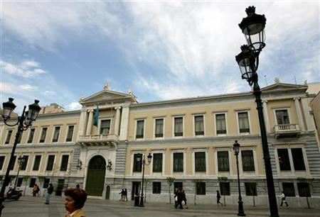 People walk outside central building of National Bank of Greece in Athens